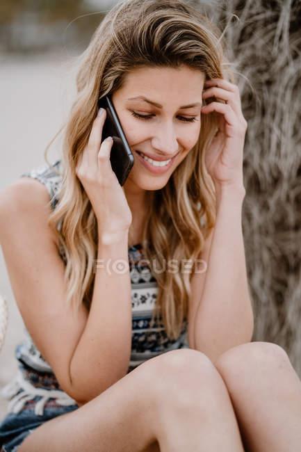 Молодая привлекательная женщина с длинными волосами отдыхает на берегу моря и разговаривает по мобильному телефону в летний день — стоковое фото
