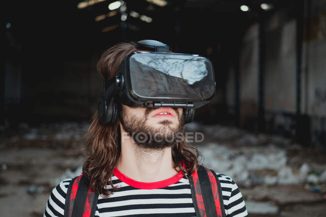 Interested young male in virtual reality glasses gesturing and exploring abandoned warehouse — Stock Photo
