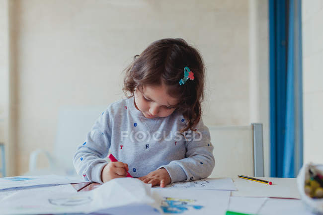 Cute curly little brunette girl in gray sweater enthusiastically drawing pencil on paper at home — Stock Photo