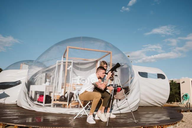 Stylish woman sitting on boyfriend lap and looking through telescope at sky near bubble hotel — Stock Photo