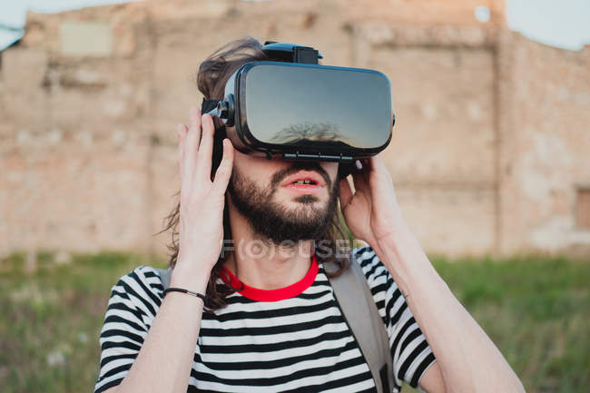 Amazed young bearded male exploring world wearing virtual reality glasses — Stock Photo