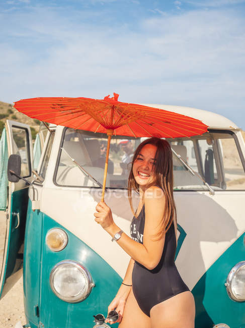 Tanned woman holding red umbrella and smiling near car at sandy beach in bright day — Stock Photo