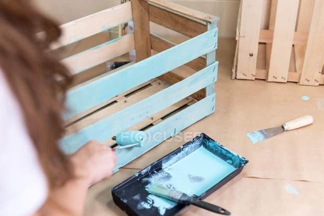 Primo piano di donna dolore scatola di legno in colore blu con rullo — Foto stock