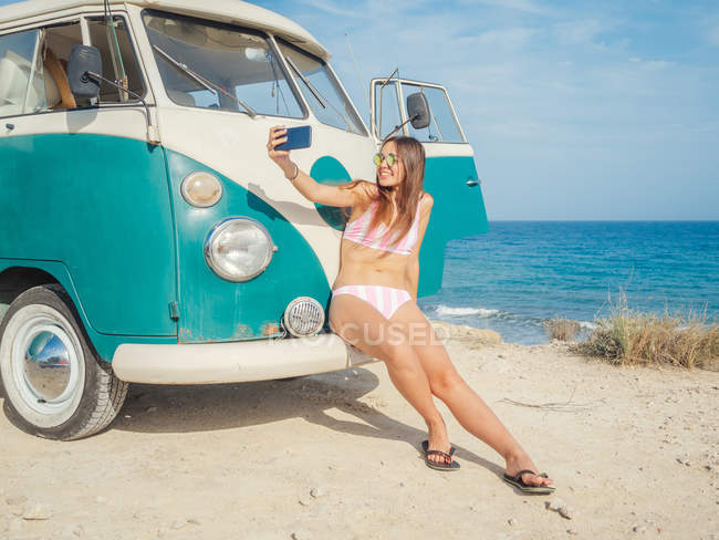 Mulher bronzeada encantadora atraente levando selfie e sorrindo perto de carro na praia de areia em dia brilhante — Fotografia de Stock