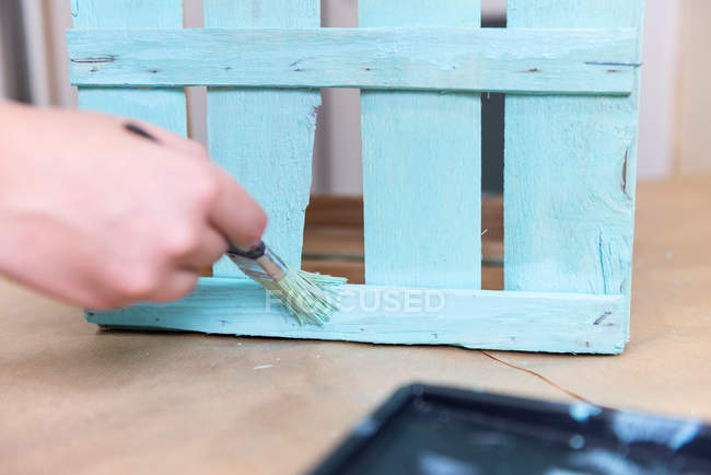 Close up da mão fêmea que doendo a caixa de madeira na cor azul com escova — Fotografia de Stock