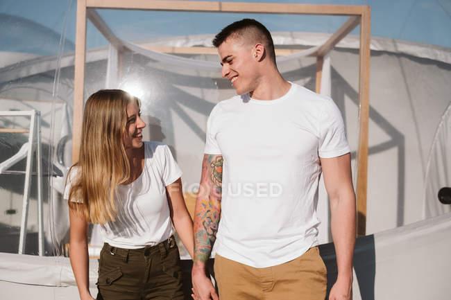 Seitenansicht eines leidenschaftlichen Mannes und einer jungen Frau, die sich vor romantischem, transparentem Glamping die Hände reichen — Stockfoto