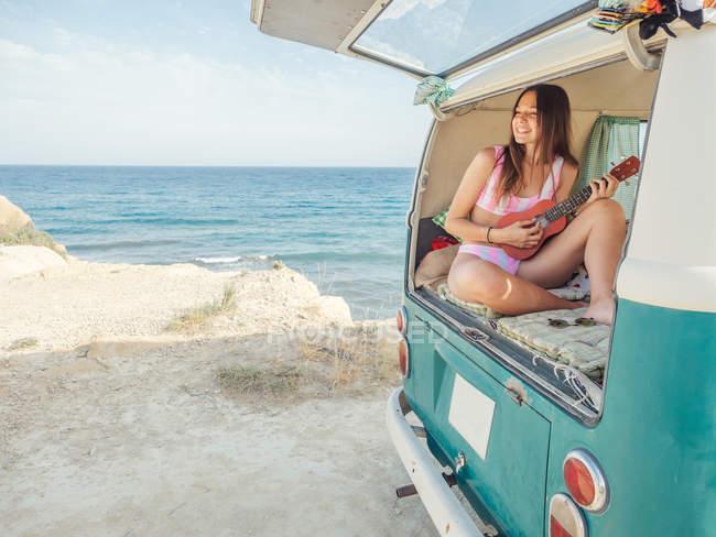 Улыбающаяся женщина в купальнике наслаждается игрой на укулеле, сидя на мягкой подушке в машине на фоне спокойной воды в спокойный день — стоковое фото