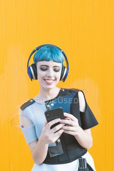 Веселая неформальная женщина в наушниках, просматривающая смартфон и слушающая музыку, стоя напротив ярко-желтой стены — стоковое фото