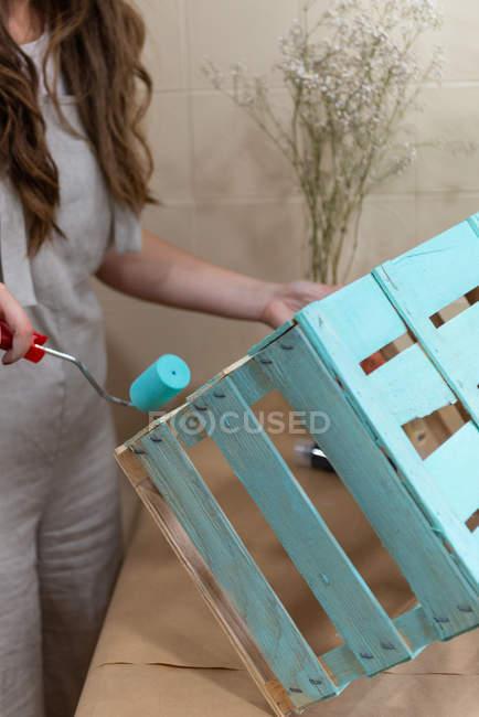 Close-up de mulher dor caixa de madeira na cor azul com rolo — Fotografia de Stock