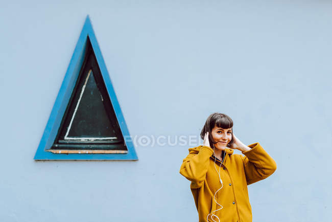Cheerful woman in yellow warm jacket smiling and touching hair while listening to music near gray building with triangle window — Stock Photo
