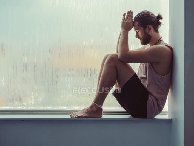 Side view of relaxed thoughtful man sitting on sill near against steamy window with eyes closed — Stock Photo
