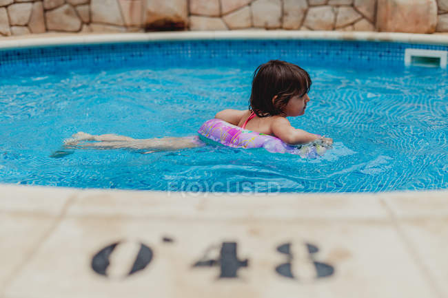 Happy adorable wet little girl in swimsuit inside swimming pool — Stock Photo
