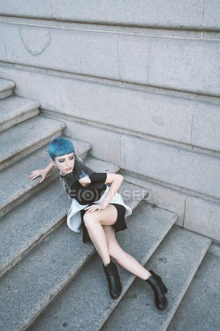 Jovem mulher com cabelo azul curto vestindo vestido informal na moda e posando em degraus de rua — Fotografia de Stock