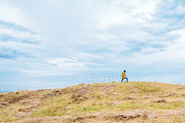 Vue latérale de la femme marchant sur le sommet d'une colline herbeuse contre le ciel nuageux à la campagne — Photo de stock