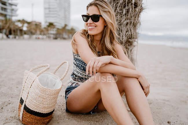 Donna bionda in occhiali da sole neri seduta sulla sabbia con borsa estiva e distogliendo lo sguardo — Foto stock