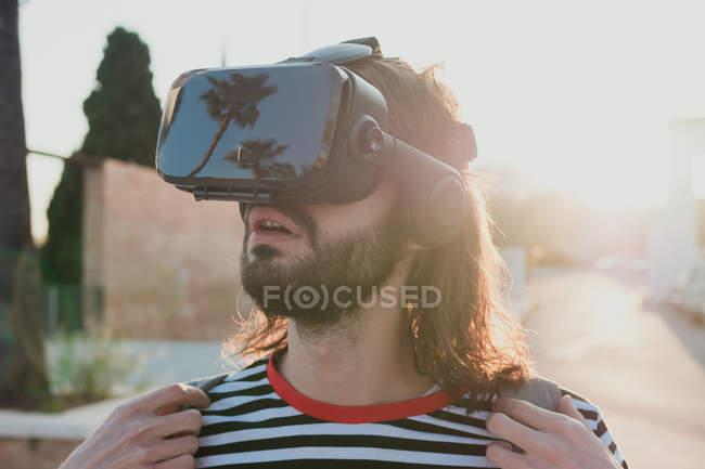Sorprendido joven barbudo explorando mundo usando gafas de realidad virtual - foto de stock