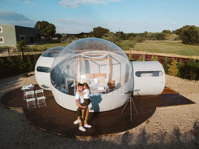 Luftaufnahme des jungen Paares küssen durch ungewöhnliche Blase Hotel — Stockfoto