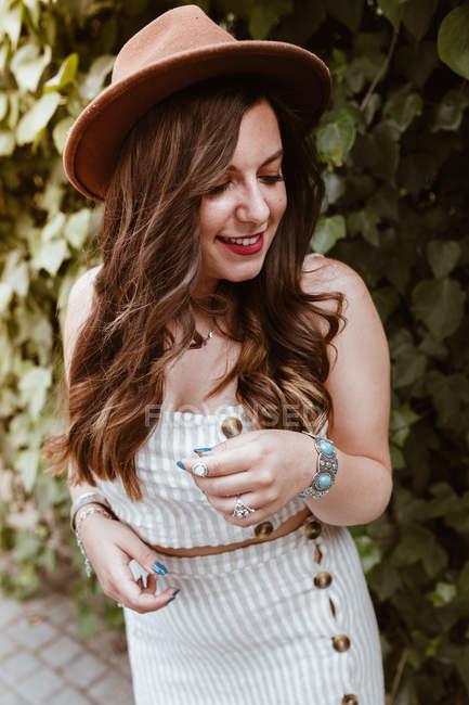 Приваблива щаслива жінка з довгим волоссям у капелюсі посеред зеленого листя. — стокове фото