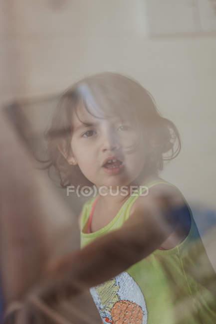Вид через окно задумчивой маленькой брюнетки, смотрящей в камеру — стоковое фото