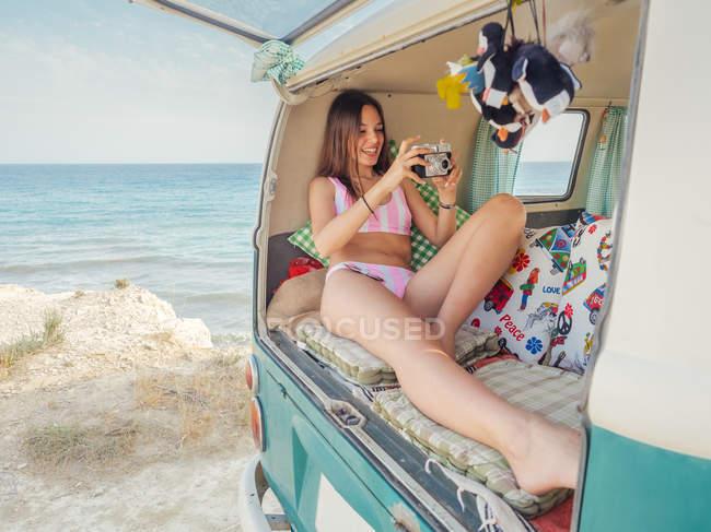 Mujer delgada en traje de baño rosa sonriendo y tomando fotos tumbada en cojines suaves en el baúl del remolque en la playa en el día soleado - foto de stock