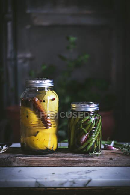 Conteneur en verre cylindrique transparent avec haricots verts marinés et légumes charnus jaunes à la cannelle disposés sur une table rustique — Photo de stock