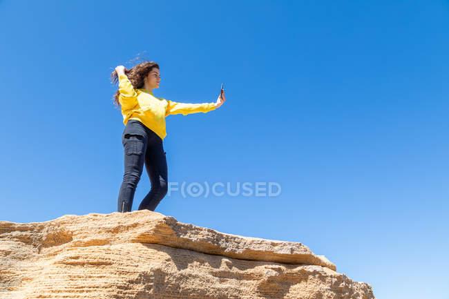 Giovane donna bruna prendere selfie con smartphone mentre in piedi su roccia arenaria scogliera contro sfondo cielo blu — Foto stock