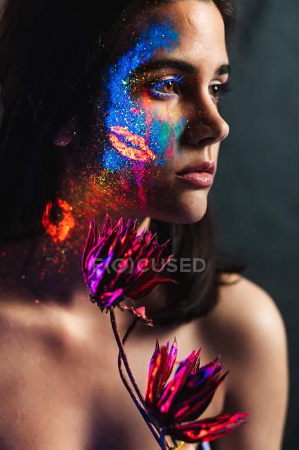 Retrato de una hermosa joven cubierta de pintura luminosa en la cara sosteniendo una flor y mirando hacia otro lado - foto de stock