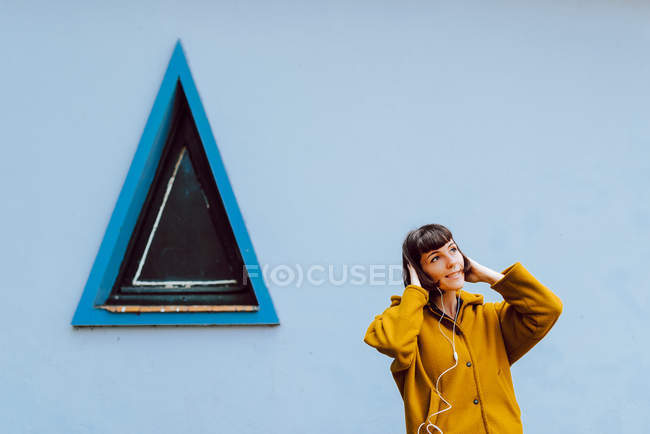 Young woman in yellow warm coat smiling and listening to the music and looking away while standing against triangle window — Stock Photo