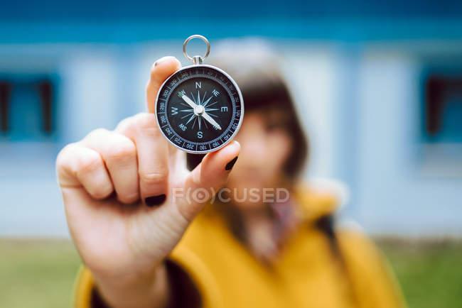 Веселая размытая молодая женщина держит ретро компас возле лица, стоя на размытом фоне загородного дома — стоковое фото