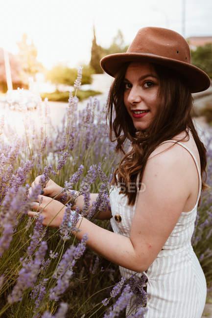Приваблива жінка з довгим волоссям у капелюсі насолоджується лавандою і посміхається перед камерою. — стокове фото