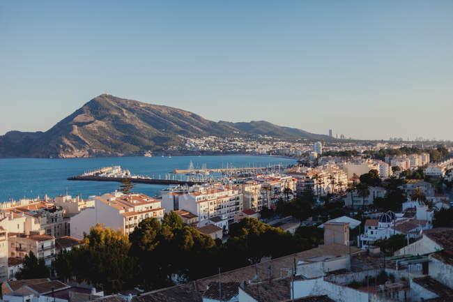 Veduta panoramica aerea di tetti di case sulla riva dell'oceano circondata da montagne con tempo soleggiato con cieli azzurri Altea, Spagna — Foto stock