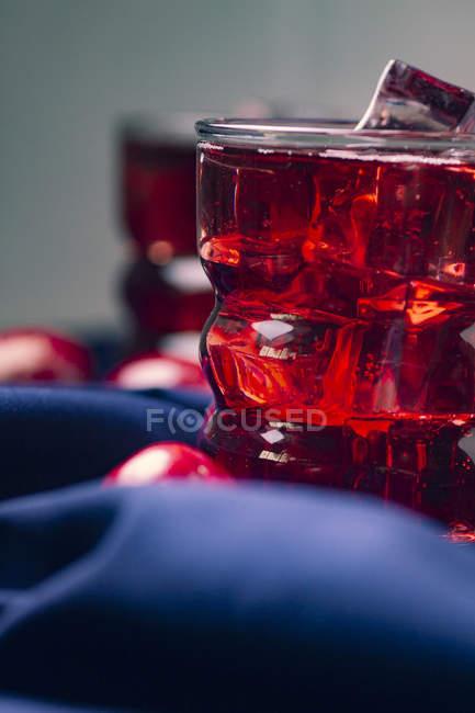 Rotes Getränk in der Nähe frischer Früchte auf blauem Tuch — Stockfoto
