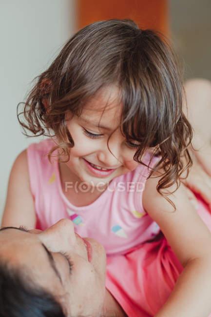Vista laterale della giovane donna bruna felice con il bambino che si diverte mentre si siede sul letto a casa — Foto stock