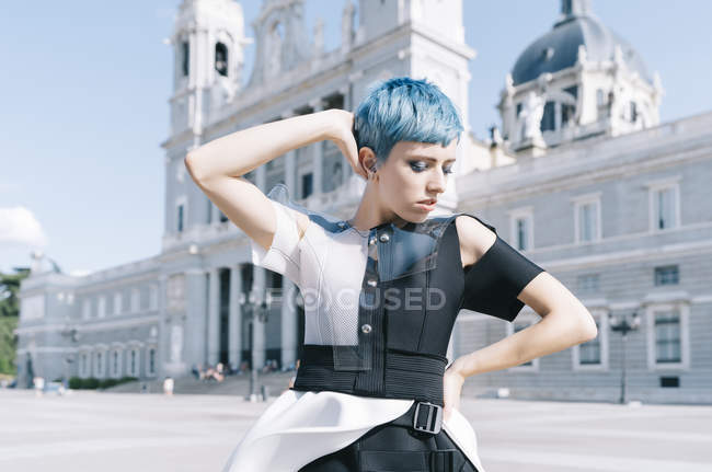 Young woman in trendy futuristic dress holding hand on waist and touching short blue hair while standing on city street — Stock Photo