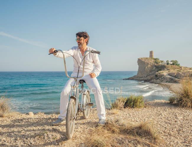 Ältere bärtige sportliche Mann mit Sonnenbrille beim Radfahren am Meer mit trockenem Gras vor dem Hintergrund der erstaunlichen türkisfarbenen Meereslandschaft in hellem Tag — Stockfoto