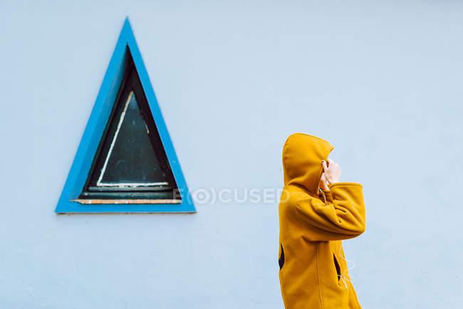 Seitenansicht der Frau Anpassung Kapuze der gelben Jacke, während sie gegen graue Wand des Gebäudes mit Dreieck-Fenster stehen — Stockfoto