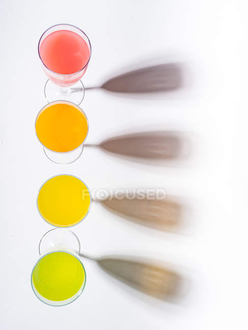 Kontrastierende Schatten aus Gläsern mit saftigen, appetitanregenden orangefarbenen, gelb-grünen Getränken auf weißem Hintergrund — Stockfoto