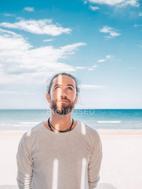 Красивый взрослый бородатый мужчина, расслабленный на берегу моря, смотрит вверх. — стоковое фото