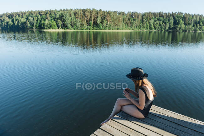 Side view of young woman in black swimsuit and hat sitting on wooden pier on the mobile phone on a lake on clear blue sky and forest background — Stock Photo