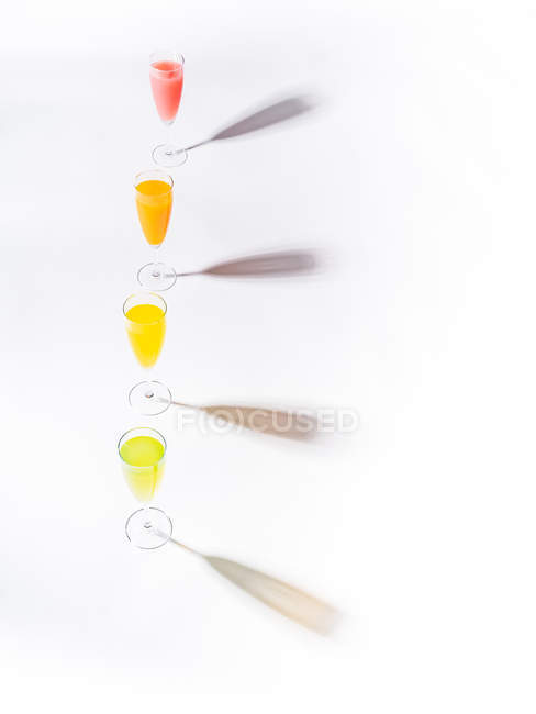 Contrasting shadows from glasses of juicy appetizing orange red yellow green drinks on white background — Stock Photo