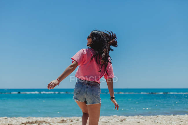 Back view of young brunette female in sunglasses short jeans and pink t-shirt dancing against blue sky and sea background — Stock Photo
