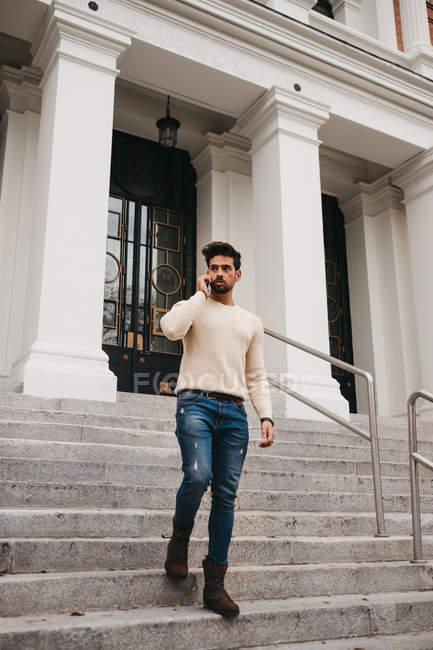 Стильный бородатый мужчина, стоящий на лестнице, разговаривающий по мобильному телефону на улице — стоковое фото