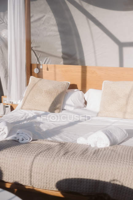 Geschminktes Bett mit weißer Bettwäsche und beigen Kissen unter transparentem Dach am sonnigen Tag — Stockfoto