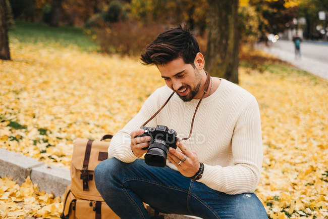 Handsome young photographer in autumn park watching photos on camera — Stock Photo