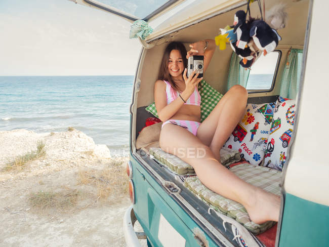 Woman in pink swimsuit smiling and taking photo lying on soft cushions in trailer trunk at seaside in sunny day — Stock Photo