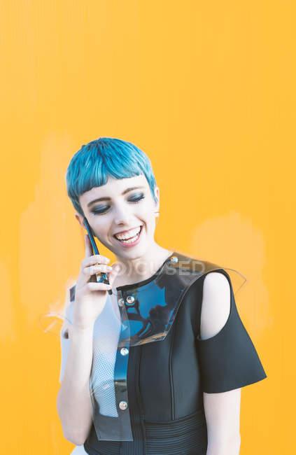 Jovem mulher em vestido futurista rindo e respondendo telefonema enquanto está de pé contra a parede amarela brilhante — Fotografia de Stock