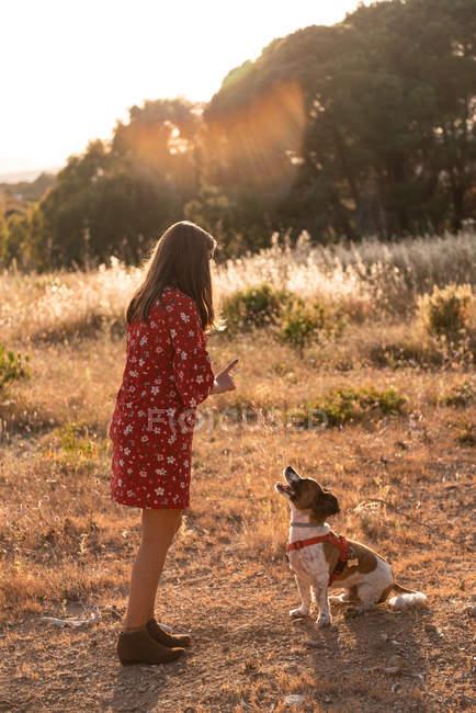 Giovane donna con i capelli lunghi che gioca con cane carino in natura — Foto stock