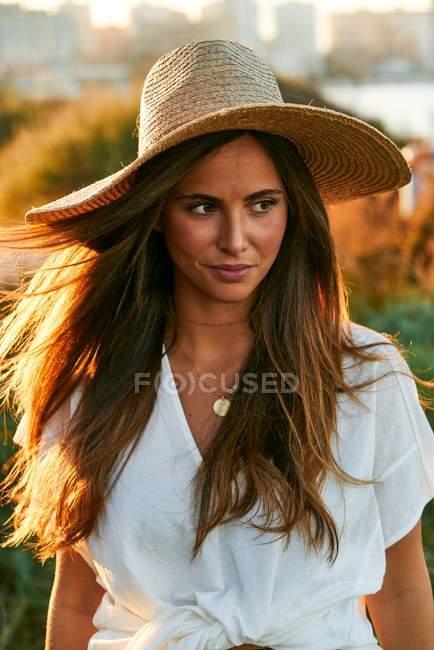 Giovane attraente modello femminile in abiti bianchi sorridente e guardando altrove — Foto stock