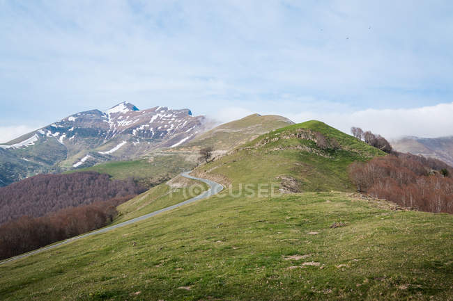 Narrow winding road going on slopes of grassy hills on cloudy day in countryside — Stock Photo