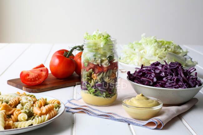 Massa gostosa com legumes frescos e molho colocado dentro jar na mesa branca — Fotografia de Stock